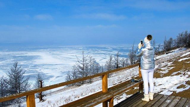 Туристка фотографирует на смартфон зимний пейзаж озера Байкал