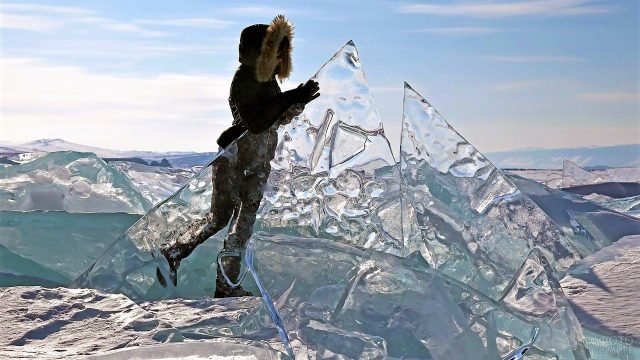 Туристка на фоне прозрачного льда на зимнем Байкале