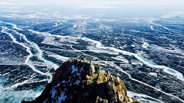 Туристы на скале над льдами зимнего Байкала