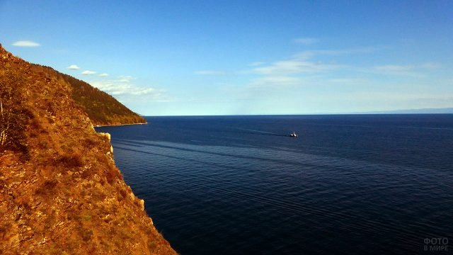 Вид с берега на корабль среди синевы вод озера Байкал