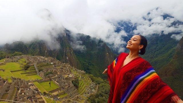 Девушка улыбается в национальном пончо на фоне древнего города