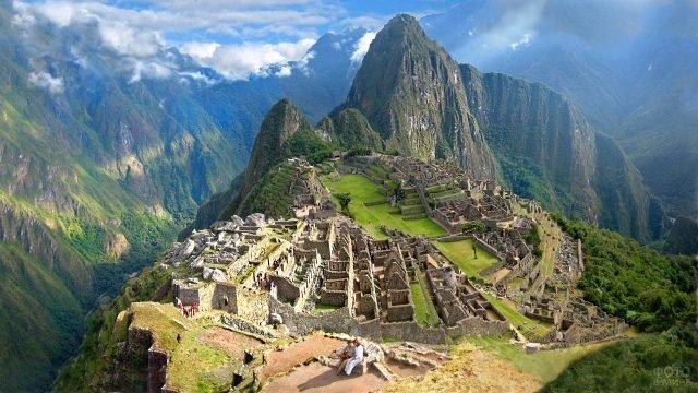 Две туристки сидят на фоне панормамы древнего города