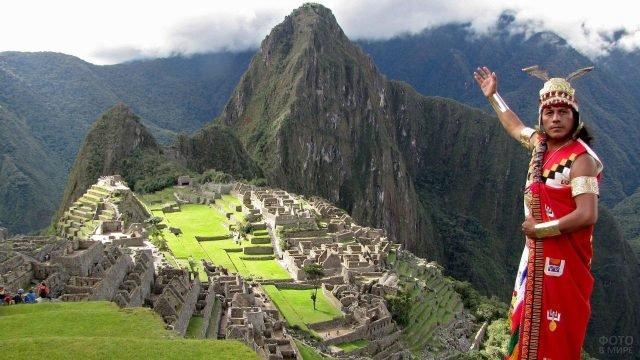 Гид в национальном костюме показывает на древний город