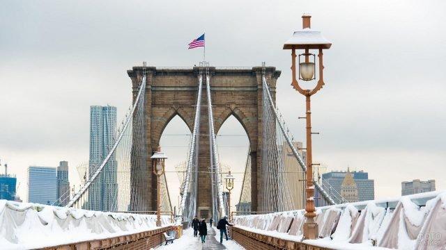 Люди идут по снежному мосту
