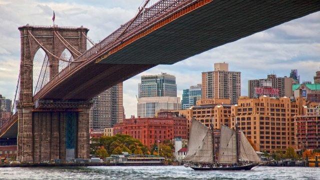 Парусник проплывает под красивым кирпичным Бруклинским мостом