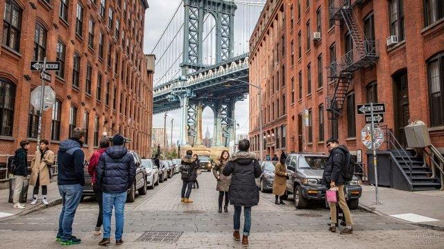 Туристы фотографируются на фоне Бруклинского моста