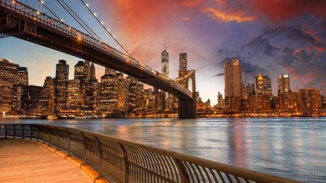 Вид с набережной на мост и красивый город вдали
