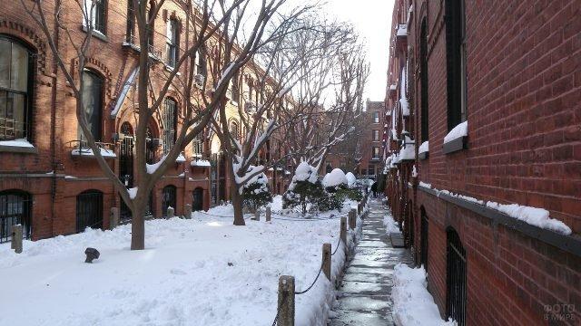 Заснеженный переулок между домами в Бруклине