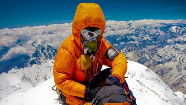 Альпинист в оранжевом костюме на вершине Эвереста