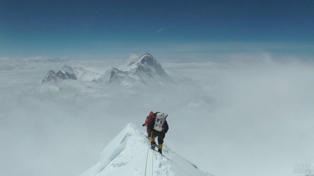 Альпинисты на снежном пике в молочных облаках
