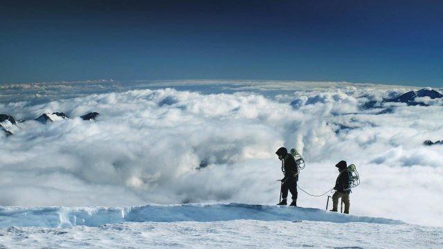 Два альпиниста в связке на фоне облаков