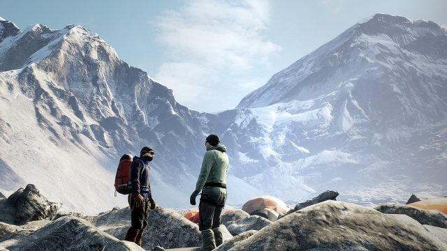 Два туриста в базовом лагере на фоне гор