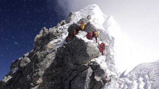 Группа альпинистов на вертикальном подъёме в снег