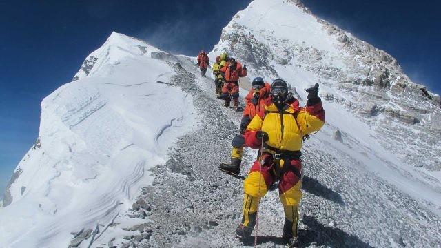 Туристы в желтых и красных костюмах на тропе подъёма на высоте более 8000 метров