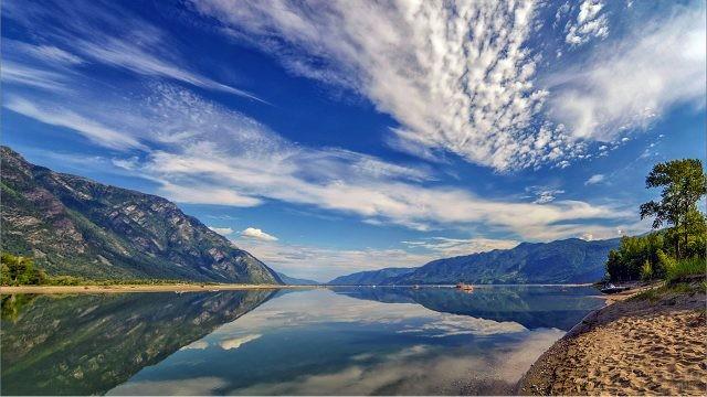 Небо отражается в зеркале воды Телецкого озера среди Алтайских гор