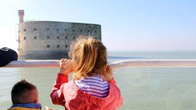 Светловолосая девочка смотрит через перила кораблика на Форт Боярд