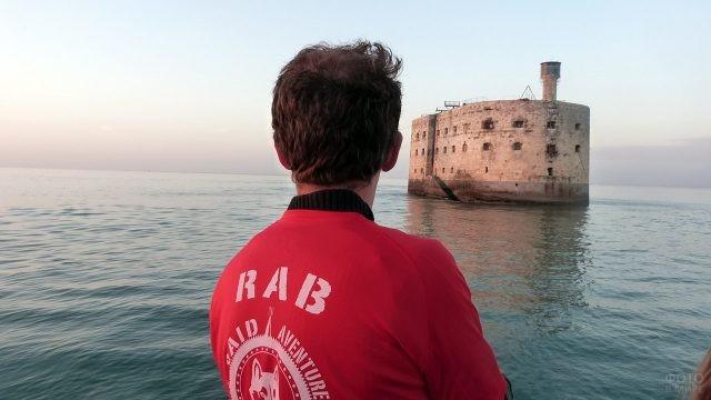Турист в красной футболке смотрит на Форт Боярд