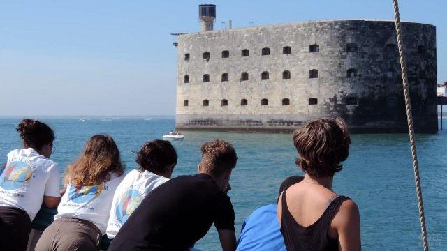 Туристы смотрят на Форт Боярд с палубы яхты