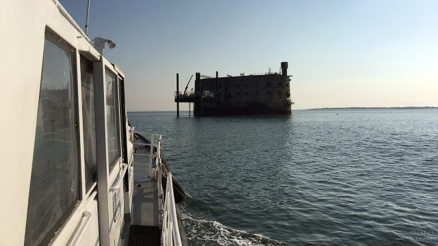 Вид на тёмный силуэт Форта Боярд с палубы катера