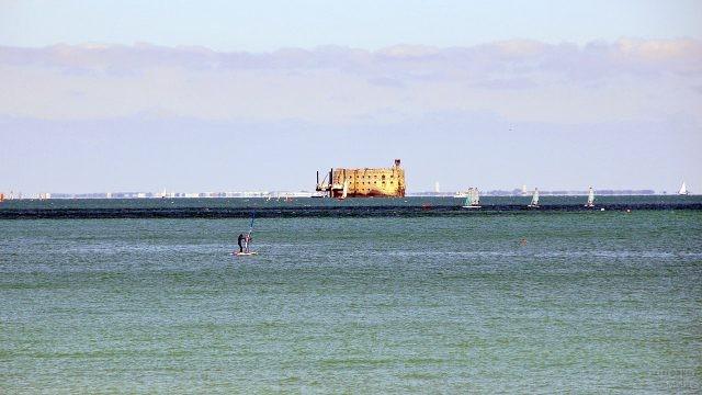 Виндсёрфер на морской панораме с Фортом Боярд на горизонте