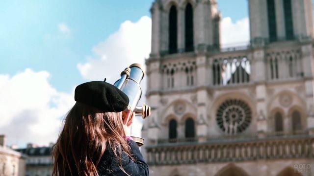 Девочка в берете разглядывает Нотр Дам де Пари через бинокуляр