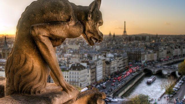 Гаргулья собора Парижской Богоматери над панорамой вечернего Парижа