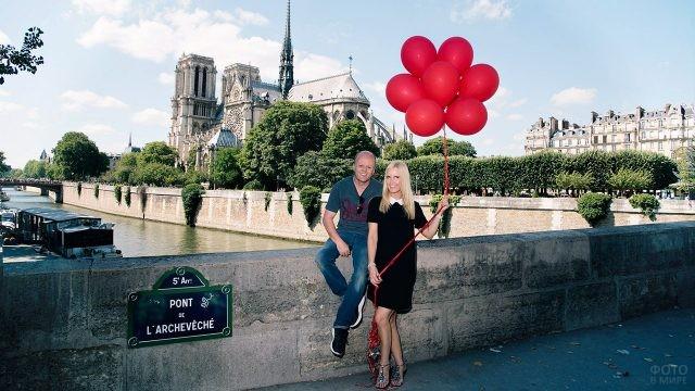 Парочка с воздушными шариками на мосту у Нотр Дам де Пари