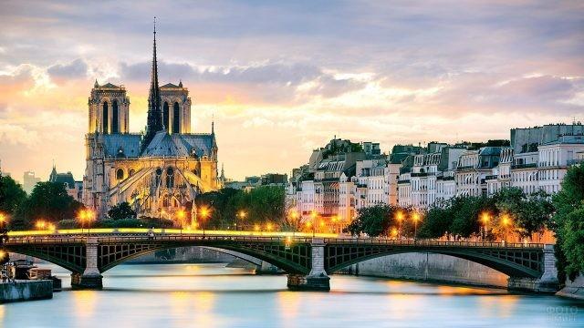 Собор Парижской Богоматери в вечерних огнях набережной Сены