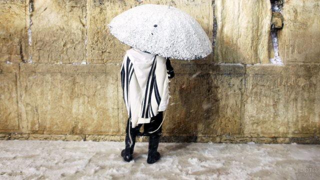 Паломник с зонтом под снегопадом у Стены Плача