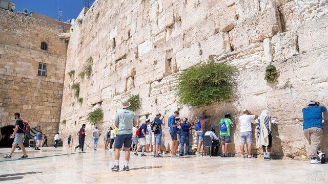 Туристы молятся и кладут записки с желаниями у Стены Плача