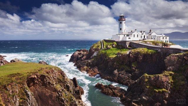 Красивый белый маяк у бушующего океана