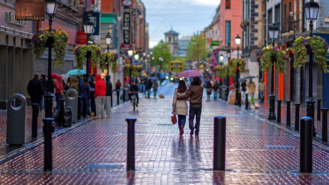 Люди гуляют по красивой и яркой улице