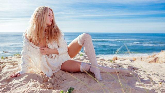 Блондинка лежит на осеннем пляже в белой одежде и чулках