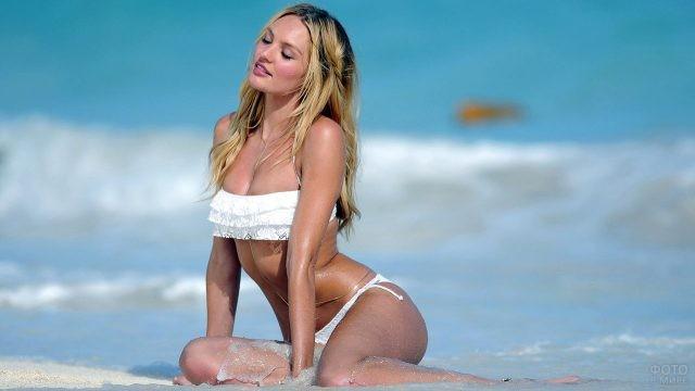 Блондинка в белом купальнике сидит на пляже на фоне волн