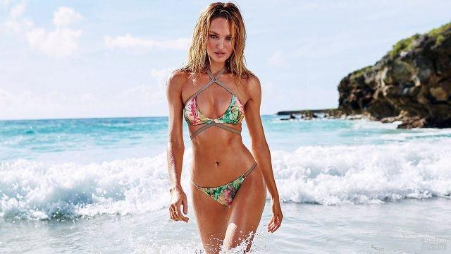 Блондинка в тропическом купальнике выходит на пляж из морских волн