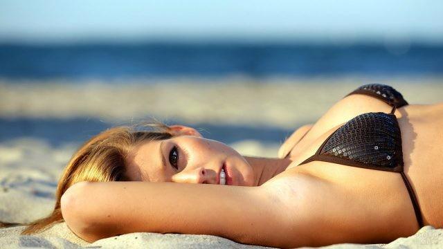 Блондинка выглядывает из-за руки, лёжа на приморском песке