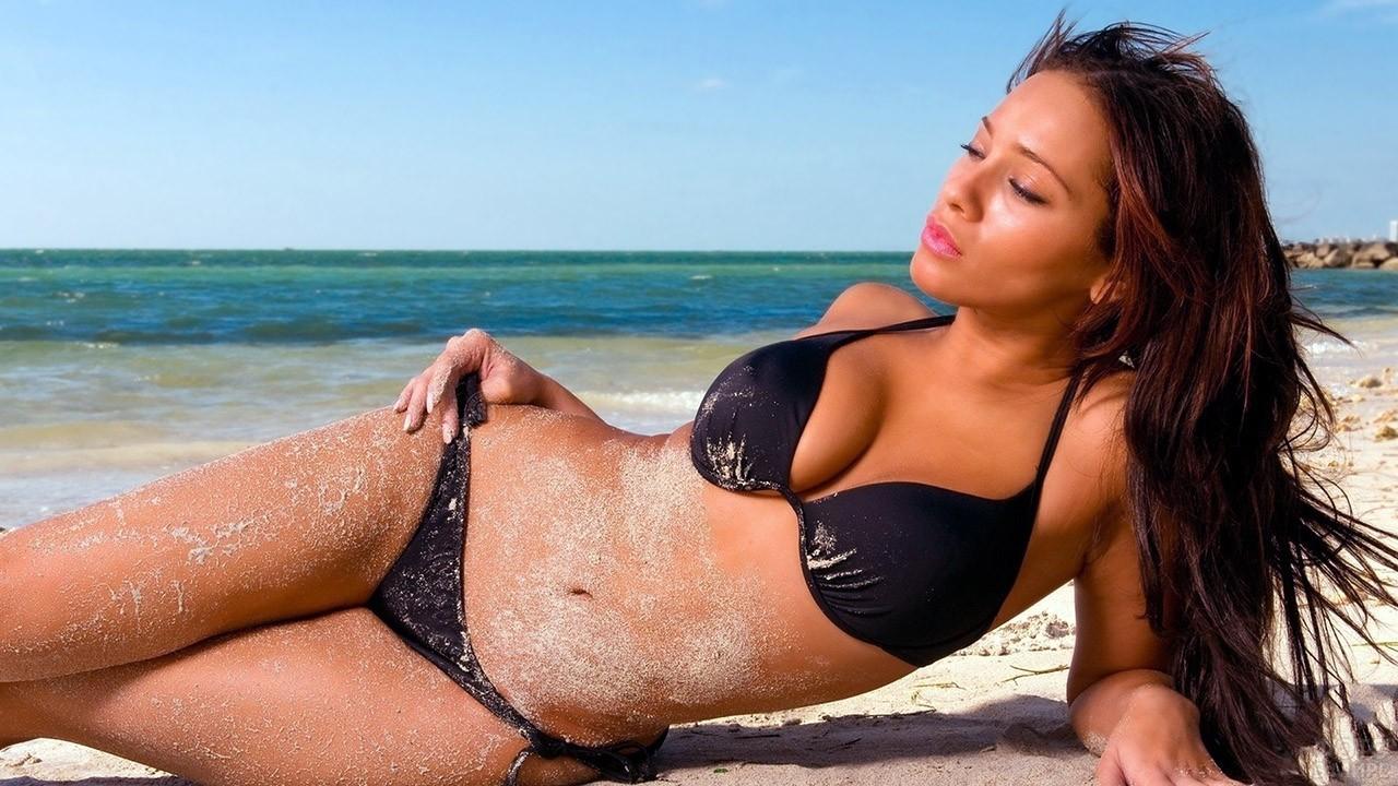 Брюнетка с развевающимися волосами лежит на песчаном пляже