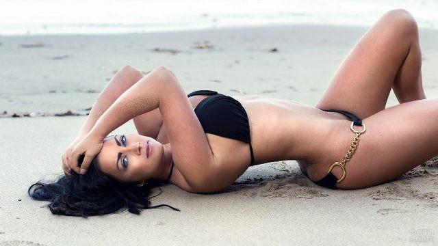 Брюнетка в бикини лежит на песчаном пляже