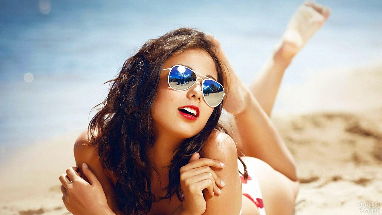 Брюнетка в солнечных очках лежит на приморском песке