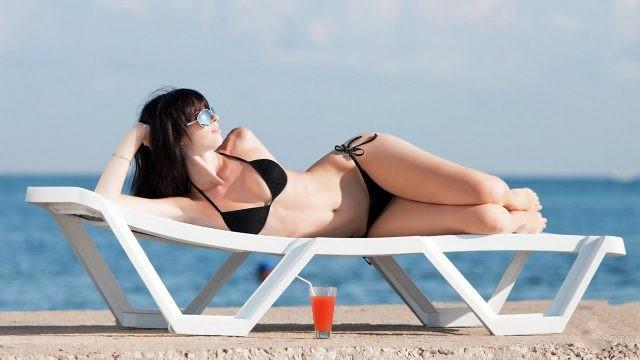 Девушка лежит на шезлонге у моря
