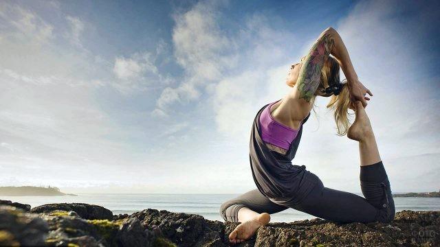 Девушка в позе йоги на каменистом пляже