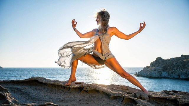 Девушка в развевающейся тунике в позе йоги на морском пляже