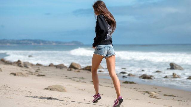 Девушка в шортах и кофте бежит по песчаному пляжу