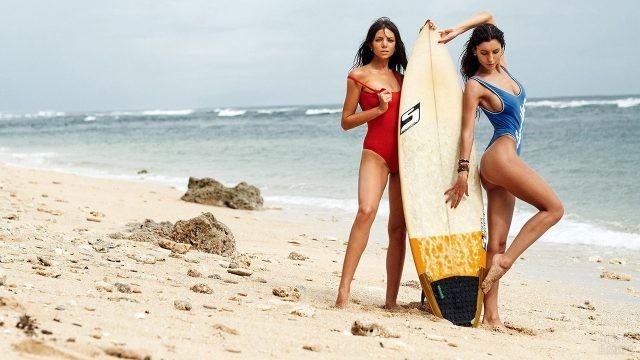 Девушки в спортивных купальниках стоят с доской для сёрфинга на песчаном пляже
