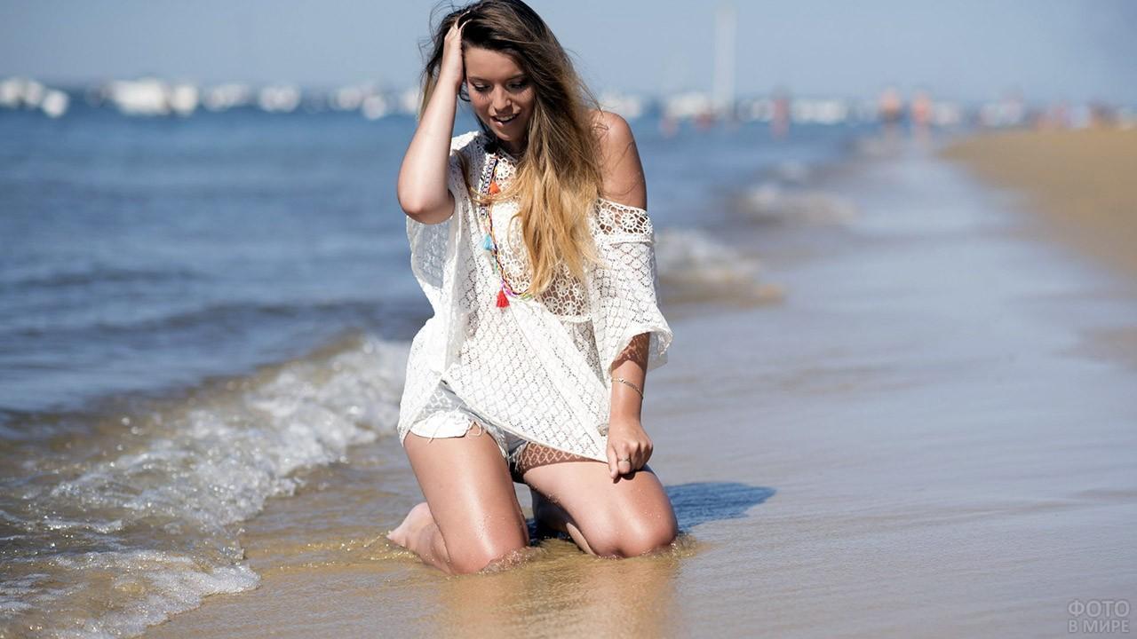Длинноволосая девушка в белой тунике сидит у кромки воды на пляже