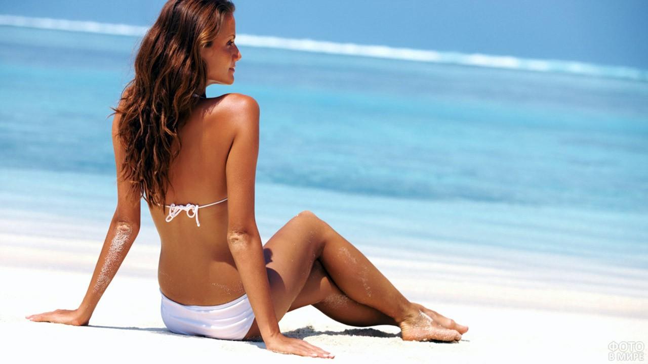 Длинноволосая девушка в белом купальнике спиной, сидя на песке у моря