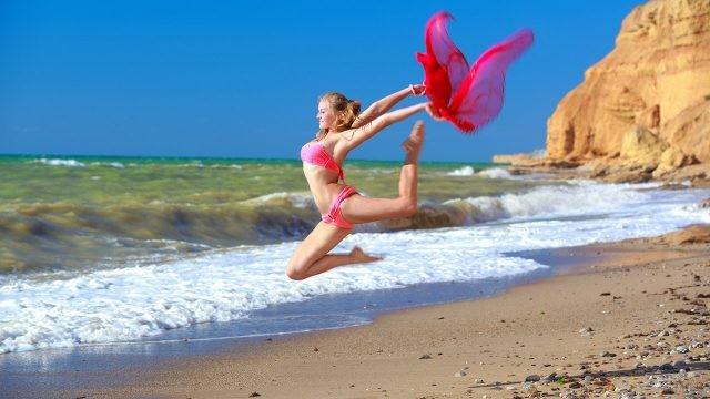 Гимнастка в алом купальнике с развевающимся платком в прыжке над пляжем