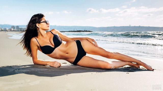 Гламурная брюнетка лежит на песчаном пляже