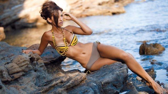 Гламурная фотомодель сидит на каменистом морском пляже