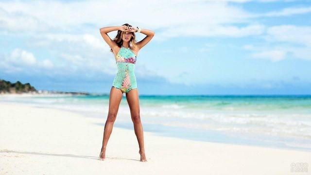 Модель в бирюзовом купальнике стоит на песчаном пляже